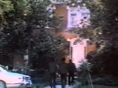 Rear view of four people walking towards brick house, 1970s Stock Footage