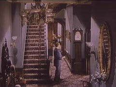 Full length shot of man adjusting time on grandfather clock in home, 1940s Stock Footage