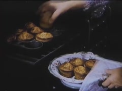 Medium shot of woman taking muffins out of oven, 1940s Stock Footage