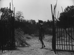 Native guarding entrance to settlement as person sneaks behind him, 1940s Stock Footage