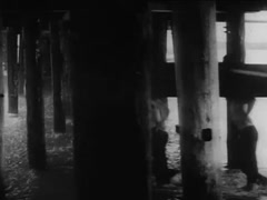 Workers carrying large log through water and wood posts below pier, 1930s Stock Footage