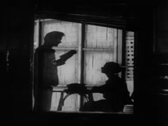 Silhouette of man reading to woman sitting at a table, 1930s Stock Footage