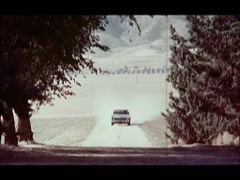 Car kicking up dust on dirt road stopping in front of house, 1970s Stock Footage