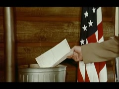 Man burning document in garbage can next to American flag, 1970s Stock Footage