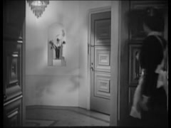 Rear view of maid opening front door of house, 1940s Stock Footage