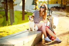 Smiling Hipster Girl with her Dog and Bike Stock Photos