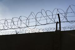 Barbed wire fence around prison walls blue sky in background Stock Photos