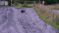 4K Mud race runner on assault course slides down hill into cold muddy water Stock Footage