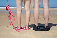 Naked couple standing on the beach with their swimmwear on their feet Stock Photos