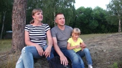 Family sitting on grass outdoors and watching the sunset. - stock footage