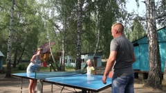 Dad and mom playing ping pong and daughter looking at the game. - stock footage