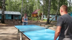 Boy and girl playing table tennis outdoors. Stock Footage