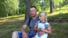 Dad and daughter sit on the grass and look into the distance. Stock Footage