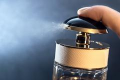 Close up of spraying perfume bottle on a dark grey background Stock Photos