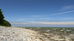 Beach scene with stones and rocks - blue sky. Rügen - Baltic Sea. Stock Footage