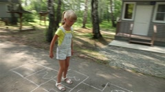 Girl playing hopscotch on the pavement. Glidecam. Stock Footage