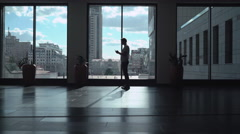 Male athletic standing near a window in a dark hallway and gaining a message on Stock Footage