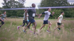4K Competitors on assault course, teammates helping each other over obstacles Stock Footage