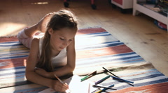 Pretty little girl drawing with color pencils on a floor in her nursery room Stock Footage