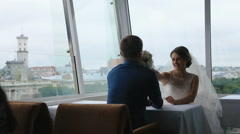 Happy young bride gives to sniff rose bouquet to groom in a cafe with panoramic Stock Footage