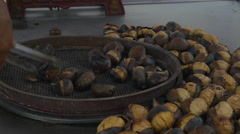 Hand roasting nuts in netted pan Stock Footage