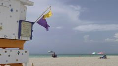 Colorful lifeguard flags waving against the shore and blue sky, Miami Beach Stock Footage