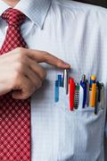 The elegant stylish businessman keeping a lot of colored pens in his breast Stock Photos