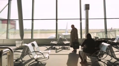 Commuters waiting at airport terminal Stock Footage