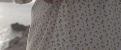 Woman unbuttoning shirt at beach Stock Footage