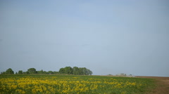 Tractor plowing a field on the background of beautiful meadows Stock Footage