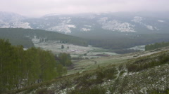Small Farm in a Mountain Valley. Early Spring Snow on the Green Grass and Stock Footage