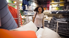 Pretty, young woman choosing a pillow - stock footage