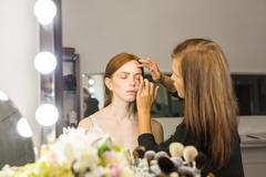 Professional Make-up artist doing glamour model makeup at work - stock photo
