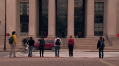 Students crossing street entering MIT building Stock Footage
