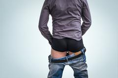 Standing man has undress jeans and peeing on blue background - stock photo
