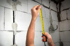 Worker with yellow tape measure in centimeters and feets measure the distance - stock photo