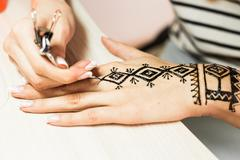 young woman mehendi artist painting henna on the hand - stock photo
