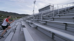Profile view of man doing sprints up bleachers Stock Footage