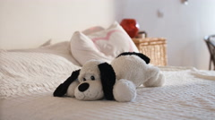 Adorable active girl sitting on the bed and playing with the soft doggy toy Stock Footage