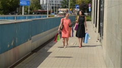 Happy friends with shopping paperbags walking in the city, beautiful women - stock footage