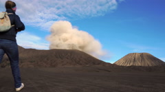 Backpacker female traveler looking at active smoking Bromo volcano in Indonesia - stock footage