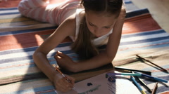 Charming girl lying on the carpet drawing with color crayons on the paper - stock footage