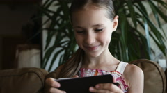 Closeup portrait child. Girl in pink clothes using mobile phone and smiling Stock Footage