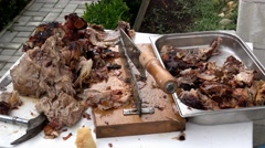 Plate full of spit grilled porky meat and equipment for cutting meat Stock Footage