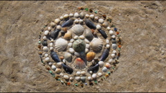 Sea shells pattern mandala appears on a sand. Stop motion animation Stock Footage