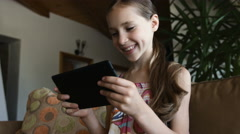 Charming girl playing tablet pc sitting on sofa in living room at home, close-up Stock Footage