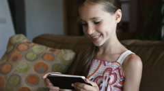 Cute smiling little girl using modern smartphone in living room, close-up - stock footage
