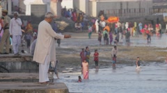 Man feeding fish in Gomti river,Dwarka,India Stock Footage