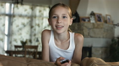 Child watching TV, little girl having fun on the couch, holding remote control - stock footage