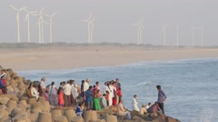 People on rocky coast with windmills,Dwarka,India Stock Footage